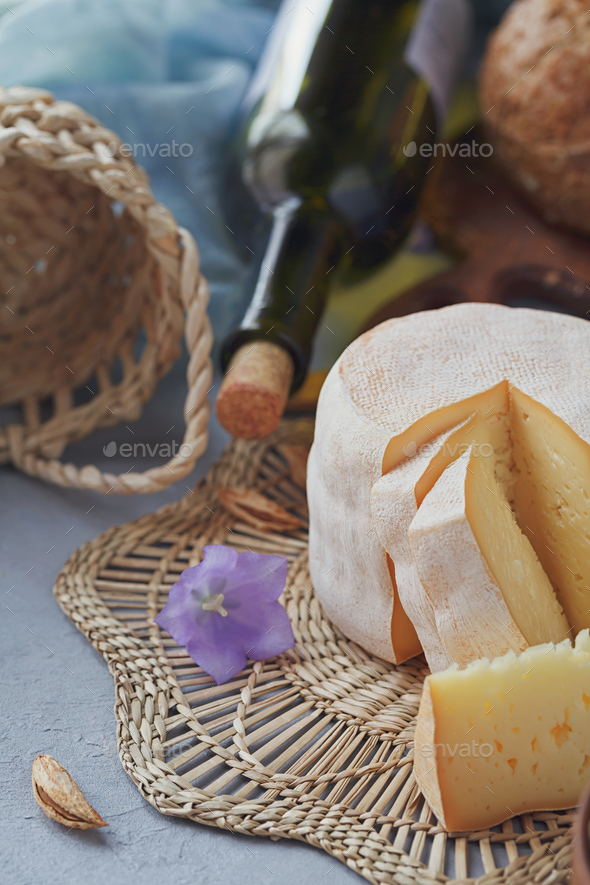 A head of fresh organic cheese served with nuts, white wine and summer flowers - Stock Photo - Images