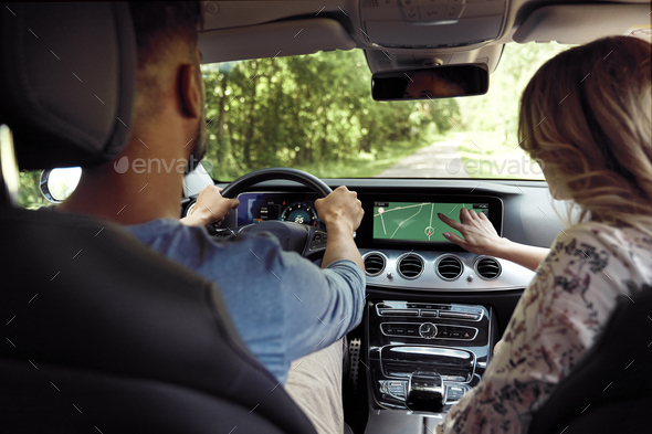 Rear view of couple driving a car on a road trip - Stock Photo - Images