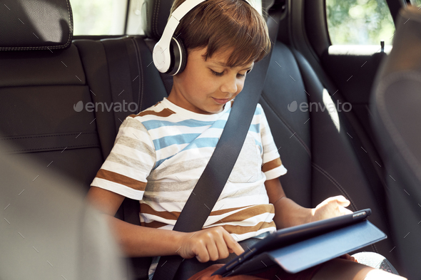 Boy sitting with a digital tablet in the car - Stock Photo - Images