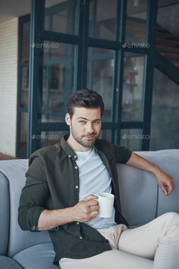 Handsome young man holding cup with drink - Stock Photo - Images