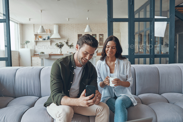 Beautiful young couple drinking coffee and communicating while sitting on the sofa at home - Stock Photo - Images