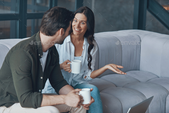 Beautiful young couple drinking coffee and communicating - Stock Photo - Images