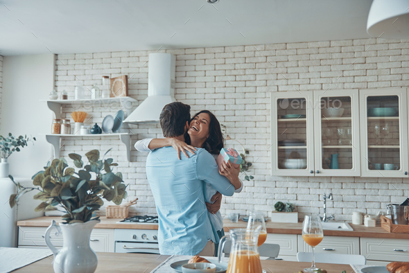 Young man giving a gift box to his girlfriend - Stock Photo - Images