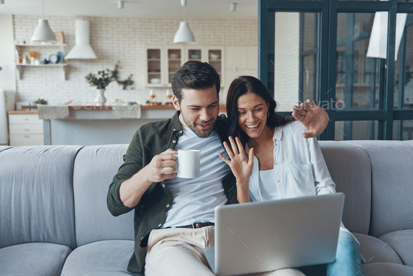 Beautiful young couple drinking coffee and looking on the laptop - Stock Photo - Images