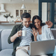 Beautiful young couple drinking coffee and looking on the laptop - PhotoDune Item for Sale
