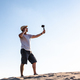 Side view of male traveler standing on sand dune and filming content for social media - PhotoDune Item for Sale