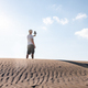 Man filming himself with his cell phone in the desert dunes. Traveling male content creator - PhotoDune Item for Sale