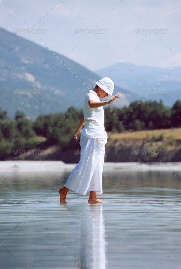 Young woman walking in lake - Stock Photo - Images