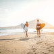 Happy surfers running with surfboards on the beach - PhotoDune Item for Sale