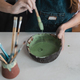 Woman mixing paint with brush inside ceramic bowl in workshop studio - PhotoDune Item for Sale