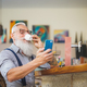 Senior man using mobile smartphone while drinking coffee in bar restaurant - PhotoDune Item for Sale