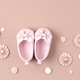 Cute newborn baby girl shoes with festive decoration over pink background. Baby shower, birthday - PhotoDune Item for Sale