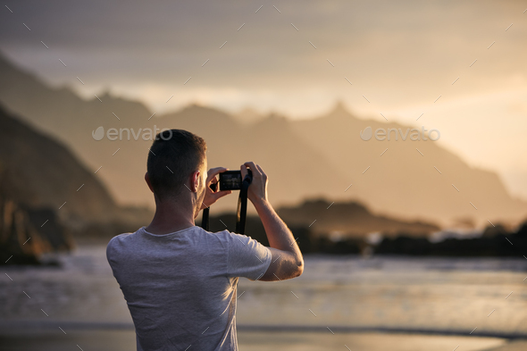 Man during photographing landscape with cliff at sunset - Stock Photo - Images