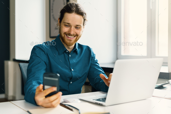 Smiling young man in casual wear looking at smartphone screen at workplace - Stock Photo - Images