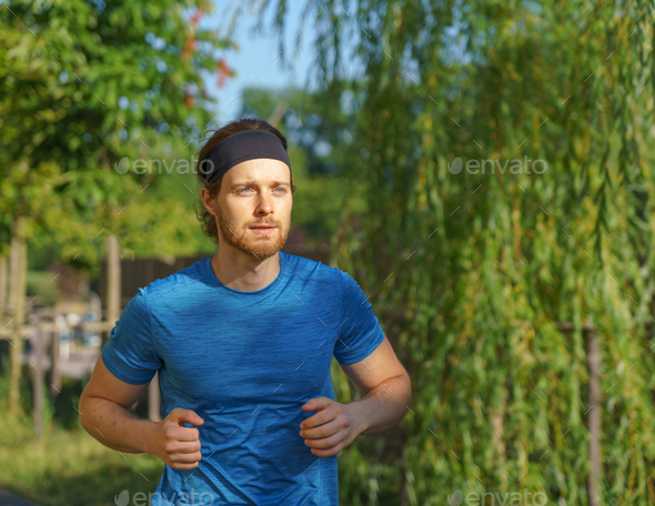 Athletic european man in sportswear jogging on road in green park on beautiful summer day - Stock Photo - Images