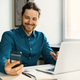Smiling young man in casual wear looking at smartphone screen at workplace - PhotoDune Item for Sale