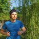 Athletic european man in sportswear jogging on road in green park on beautiful summer day - PhotoDune Item for Sale