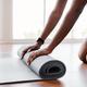 Young black woman unrolling yoga mat on floor - PhotoDune Item for Sale
