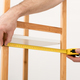 Cropped Shot Of Carpenter Measuring Wooden Shelf With Tape Indoors - PhotoDune Item for Sale