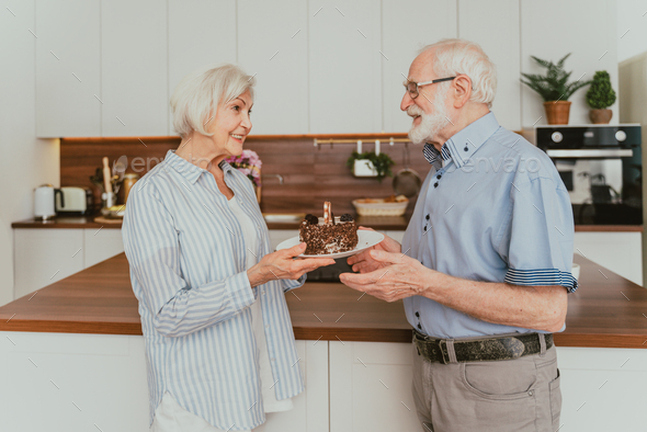 Senior couple celebrating birthday at home - Stock Photo - Images