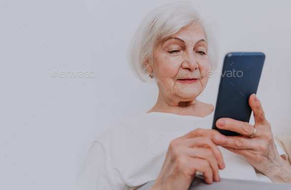 Elderly woman with smartphone at home - Stock Photo - Images