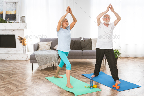 Elderly couple doing fitness at home - Stock Photo - Images
