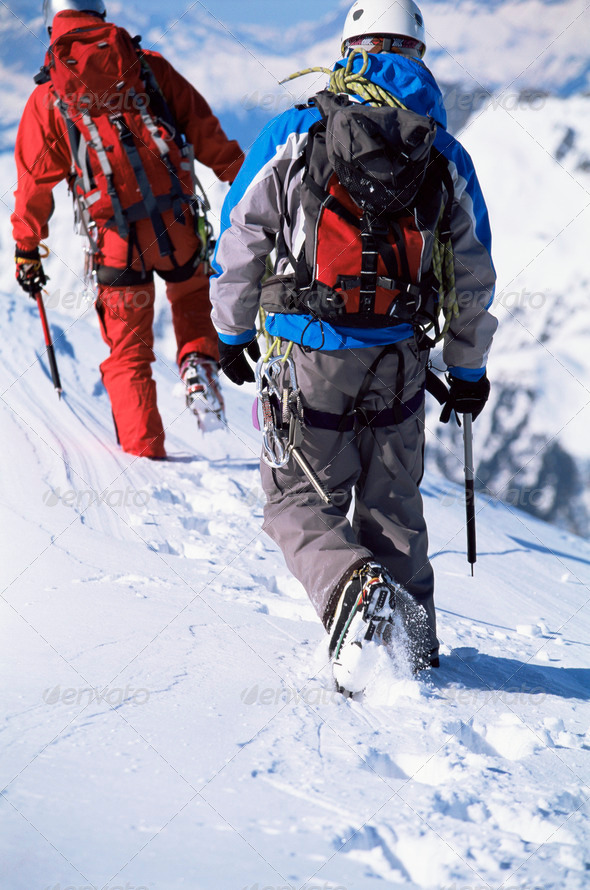 Young men mountain climbing on snowy peak - Stock Photo - Images