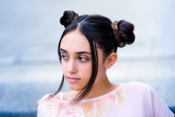 Teen girl with hair buns looking away - Stock Photo - Images