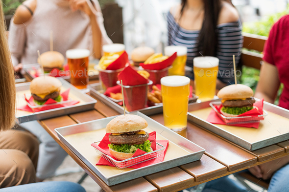 Serving of hamburgers and cold beers at a restaurant table - Stock Photo - Images