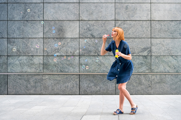 Carefree redhead woman celebrating blowing soap bubbles in town - Stock Photo - Images