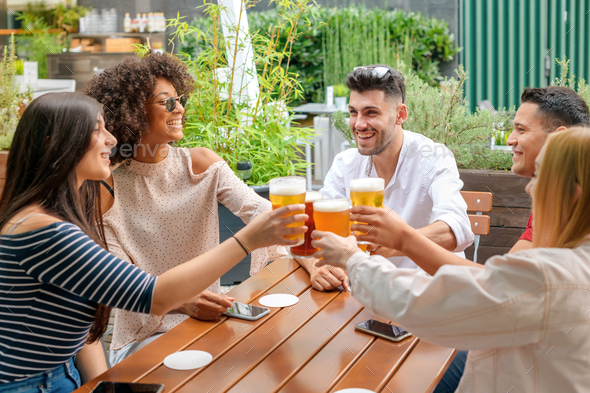 Group of friends celebrating at an open air restaurant - Stock Photo - Images