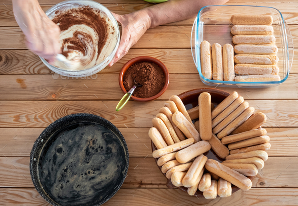 One people busy preparing a sweet tiramisu. All ingredients in the wooden table. - Stock Photo - Images