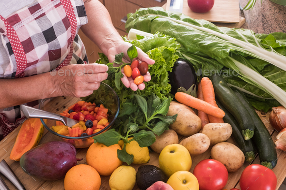 Hands of a woman cut fruit and select the best small tomatoes, wooden table with fruit and vegetable - Stock Photo - Images