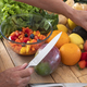 A wooden cutboard  full of fruits and vegetables. A woman prepare a vegetarian fruit salad - PhotoDune Item for Sale