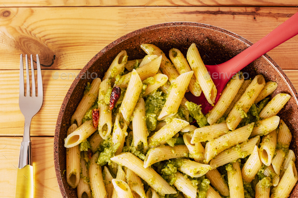Close up view of healthy and vegan pasta first course with broccoli and red pepper in a pan - Stock Photo - Images