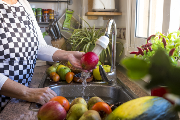 Hands of a senior woman in the kitchen washing a red apple under the running water. - Stock Photo - Images