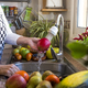 Hands of a senior woman in the kitchen washing a red apple under the running water. - PhotoDune Item for Sale
