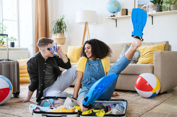 Cheerful young couple packing for summer beach holiday, coronavirus concept - Stock Photo - Images