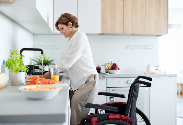 Portrait of disabled mature woman with wheelchair indoors at home, preparing breakfast - Stock Photo - Images