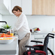 Portrait of disabled mature woman with wheelchair indoors at home, preparing breakfast - PhotoDune Item for Sale