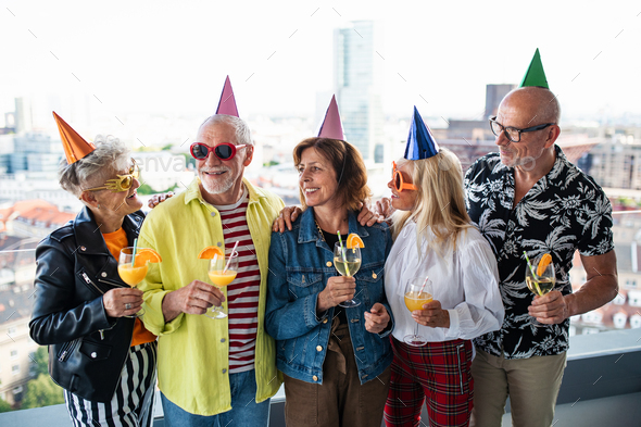 Group of senior friends having party outdoors on balcony, posing for photograph - Stock Photo - Images