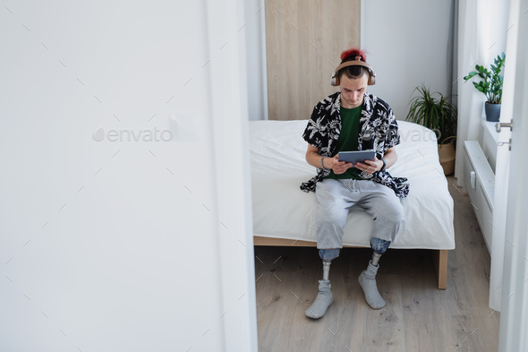 Portrait of disabled young man using tablet on bed indoors at home, leg prosthetic concept - Stock Photo - Images