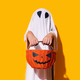Child in ghost costume holding pumpkin-shaped basket in front of him - PhotoDune Item for Sale
