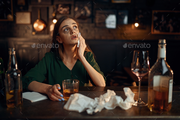Drunk depressed woman at the counter in bar - Stock Photo - Images