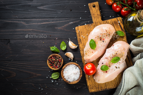 Chicken fillet with herbs and spices at wooden table - Stock Photo - Images