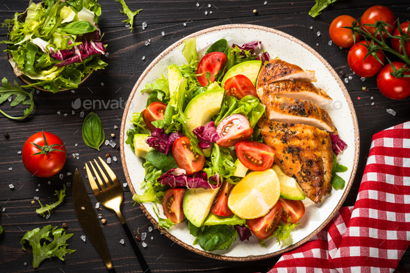 Grilled chicken with fresh salad at wooden table - Stock Photo - Images