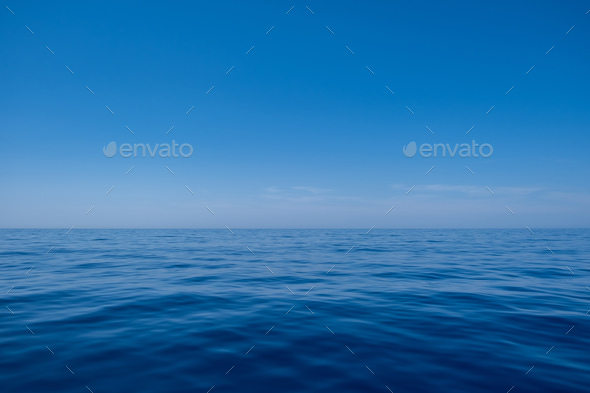 Sea water surface calm with small ripples, deep blue color and blue sky background, - Stock Photo - Images