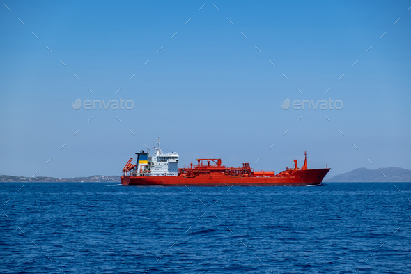 Chemical oil tanker ship, red color in blue Aegean sea and sky background. Greece - Stock Photo - Images