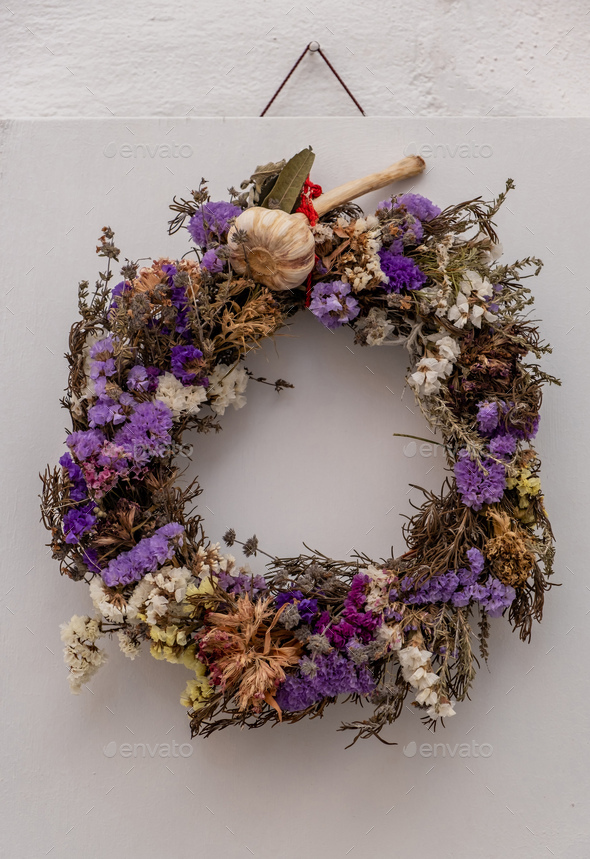 Dry flowers wreath hanging on whiteboard at Paros island Naoussa village Cyclades Greece. Vertical - Stock Photo - Images