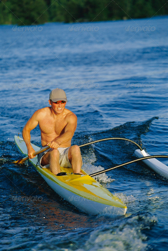 Man canoeing at sunset - Stock Photo - Images